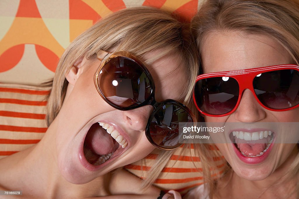 Two young women wearing sunglasses, yelling, close-up : Stock Photo
