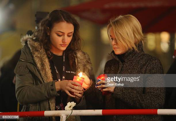 Two young women who said they did not mind being photographed light candles at a makeshift memorial the day after a truck drove into a crowded...