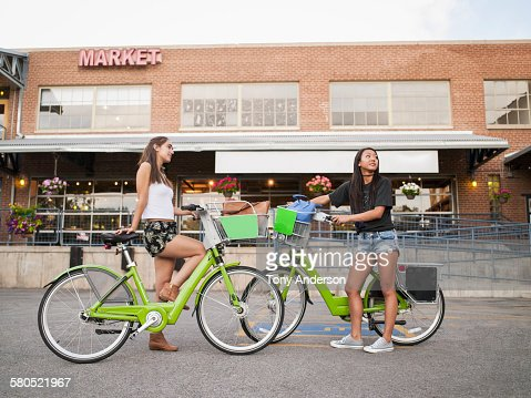 Two young women with bike shares at market