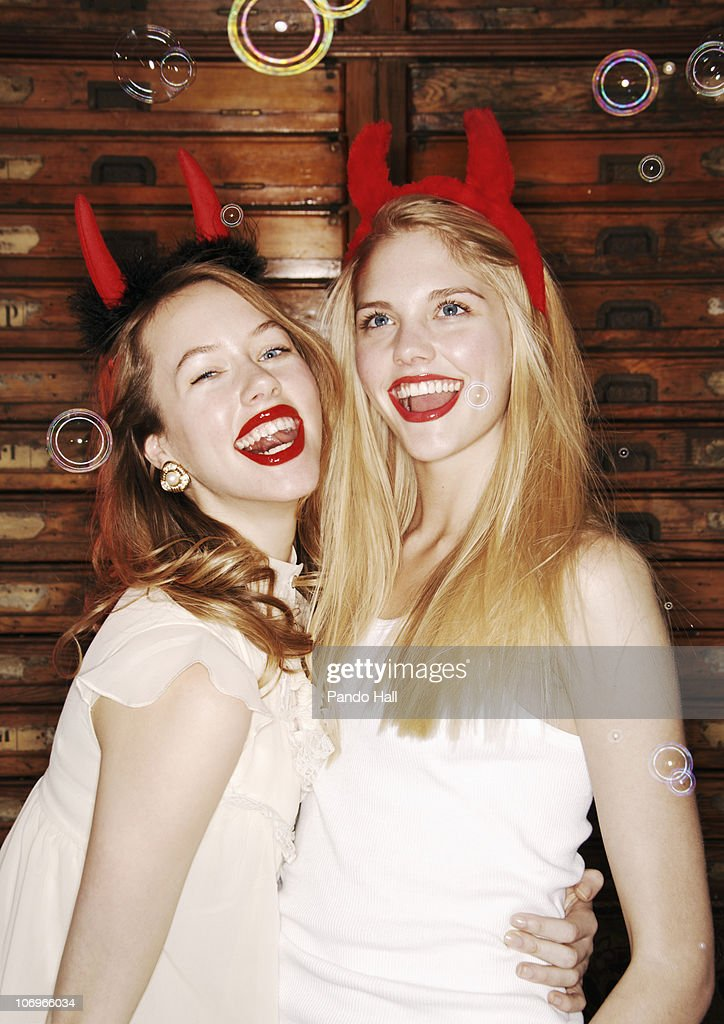 Two young women with devil horns laughing