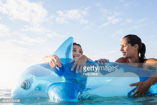 Two young women with inflatable toy in sea : Stockfoto