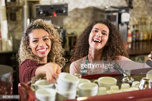 Two young women working as baristas in coffee shop : Stock-Foto