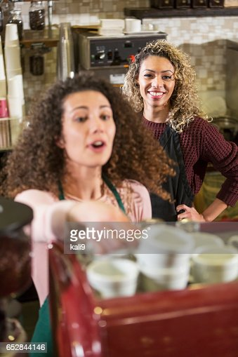 Two young women working as baristas in coffee shop : Stockfoto