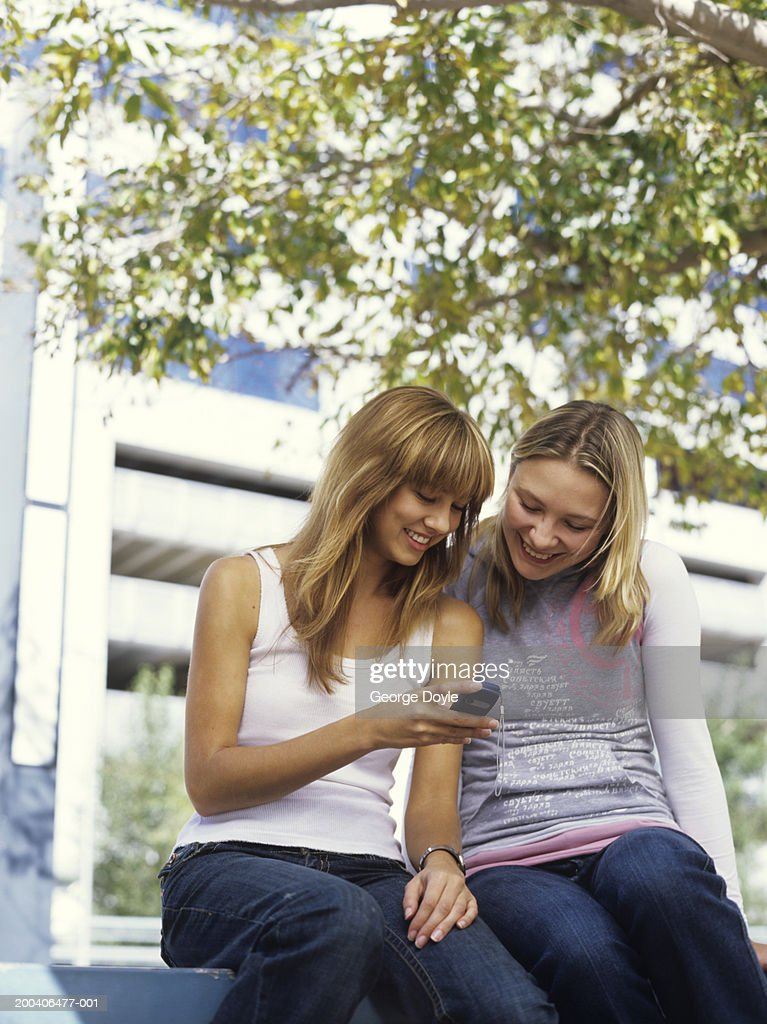 Two young womensitting on bench looking at mobile phone, low angle : Stock Photo