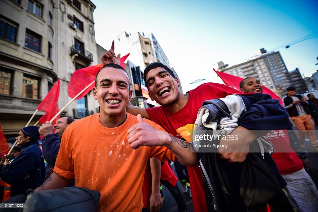 Two young workers march with enthusiasm against the economic policies in Montevideo on June 29, 2016. The PIT-CNT (the only organization of unionized workers of Uruguay) today made a partial strike and marched to front the Ministry of Economy of Uruguay.