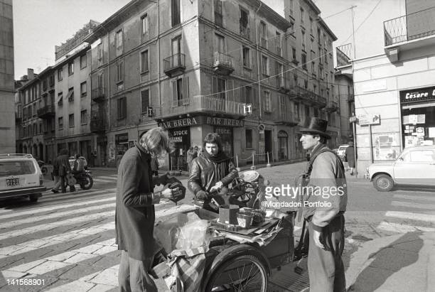 Two youngsters buying from an antique barrow interesting local characters in Brera the Latin Quarter of Milan with its luxury restaurants and...