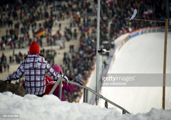 Two youngsters make their way down the hill as the start of the FIS Ski Jumping World Cup individual large hill competition has been delayed on the...