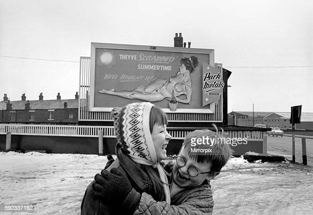 Two youngsters out playing in the snow sniggering after seeing the poster December 1970 7100003001