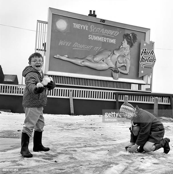 Two youngsters out playing in the snow use the poster for target practise December 1970 7100003
