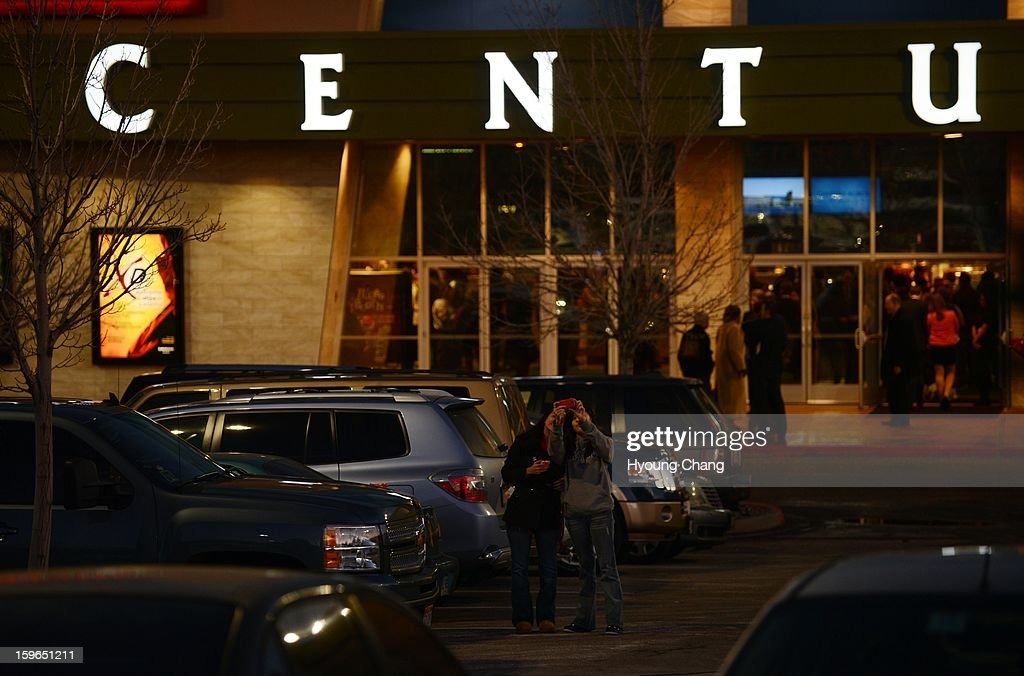 Two youths are taking picture with the Century Aurora. The movie theater where a gunman killed 12 people and wounded dozens of others reopened with a private ceremony for victims, first responders and officials.