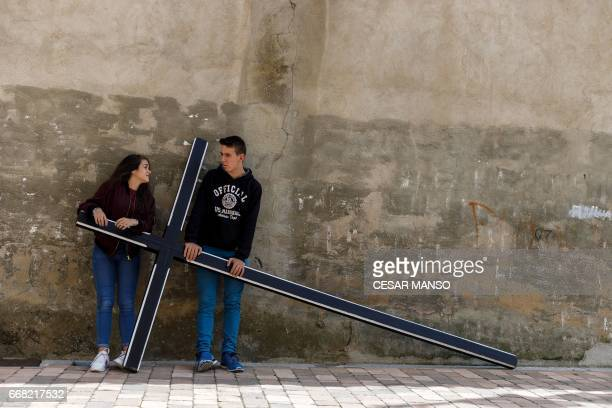 TOPSHOT Two youths hold a cross before the Ecce Homo Passion procession during Holy Week in the northwestern Spanish village of Fuentesauco on April...