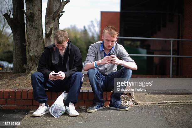 Two youths send text messages on their smart phones in Corby Northamptonshire the youth unemployment capital of Britain on April 24 2013 in Corby...