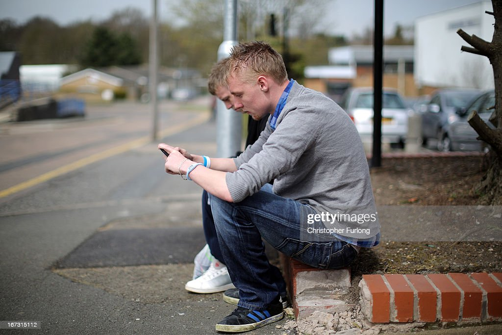Two youths send text messages on their smart phones in Corby, Northamptonshire, the youth unemployment capital of Britain, on April 24, 2013 in Corby, England. A recent study pin pointed Corby as Britain's youth unemployment capital. The study by education specialists Ambitious Minds found that youth unemployment was 11% rising from 4% in 2007. Corby in Northamptonshire was built around its steel industry in the 1930's. The steel works closed in 1980 with the loss of 10,000 jobs.