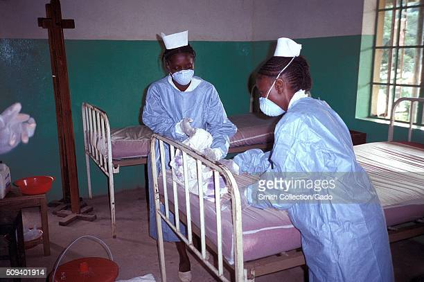Two Zairian nurses wear protective clothing while changing the bedding in an Ebola isolation ward Kikwit Zaire 1995 There is no standard treatment...