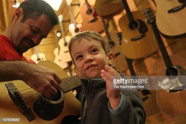 Twoandahalfyearold Samuel Godswa gets into the rhythm with a snap of his fingers as his dad Michael Godswa of northwest Washington DC strums a tune...