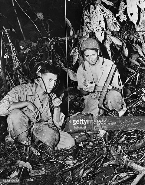 A twoman team of Navajo code talkers attached to a Marine regiment in the Pacific relay orders over the field radio using their native language The...