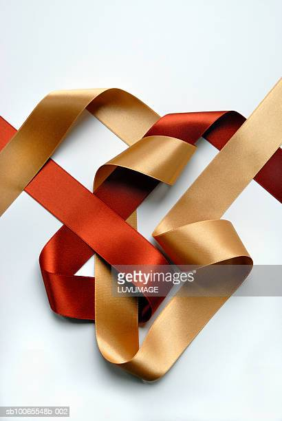 Two-sided gold and copper ribbon intertwined in abstract composition