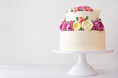 Two-tiered white wedding cake decorated with color cream flowers on a white wooden background.