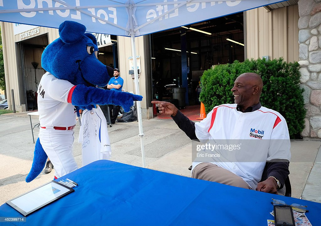 Two-time All-Star, two-time Silver Slugger Award winner and 1985 World Series Champion Willie Wilson interacts with Super Sam the Mobil mascot at a local Pitstop Automotive & Mobil Lube Express at Werner Park as part of the Mobil Super 'Go the Distance' Baseball Tour on July 19, 2014 in Omaha, Nebraska.