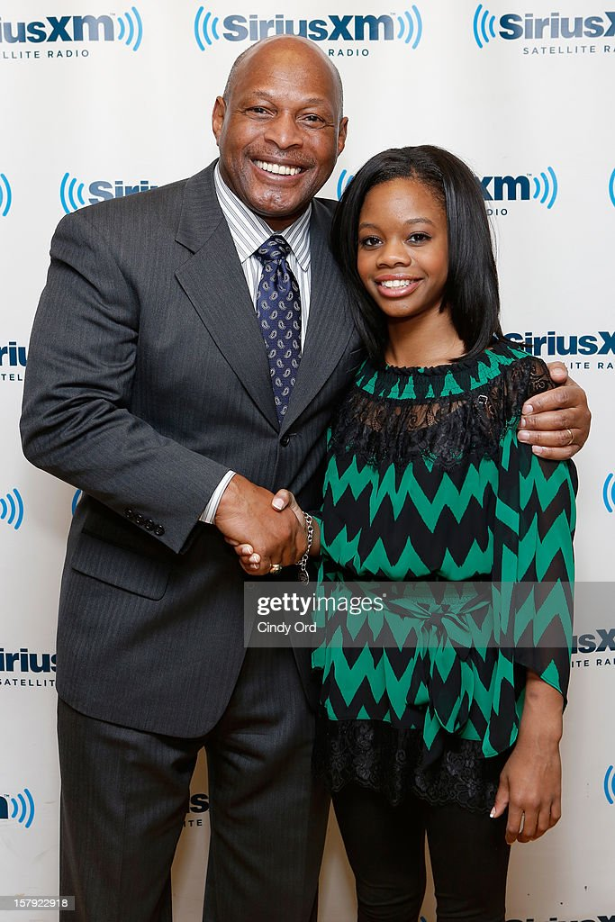 Two-time Heisman Trophy winner/ former NFL running back Archie Griffin poses with Olympic gold medalist Gabby Douglas at the SiriusXM Studios on December 7, 2012 in New York City.