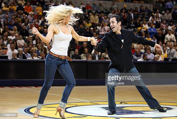 Twotime Indy 500 champion Helio Castroneves and his partner from the TV hit 'Dancing With The Stars' Julianne Hough perform during the NBA game...