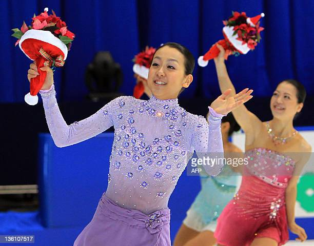 Twotime world champion Mao Asada reacts to the audience after wining Japan's national championships in Osaka on December 25 while silver medalist...