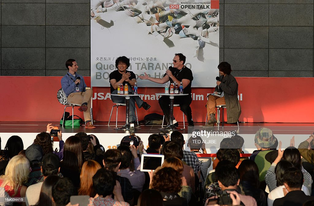 Two-times Oscar awards winner and hollywood director Quentin Tarantino (2nd R) gestures as he answers a question next to South Korean director Bong Joon-Ho (2nd L) during the open talk event at the 18th Busan International Film Festival (BIFF) in Busan on October 11, 2013. The Busan film festival is being held from October 2-12. AFP PHOTO/TED ALJIBE