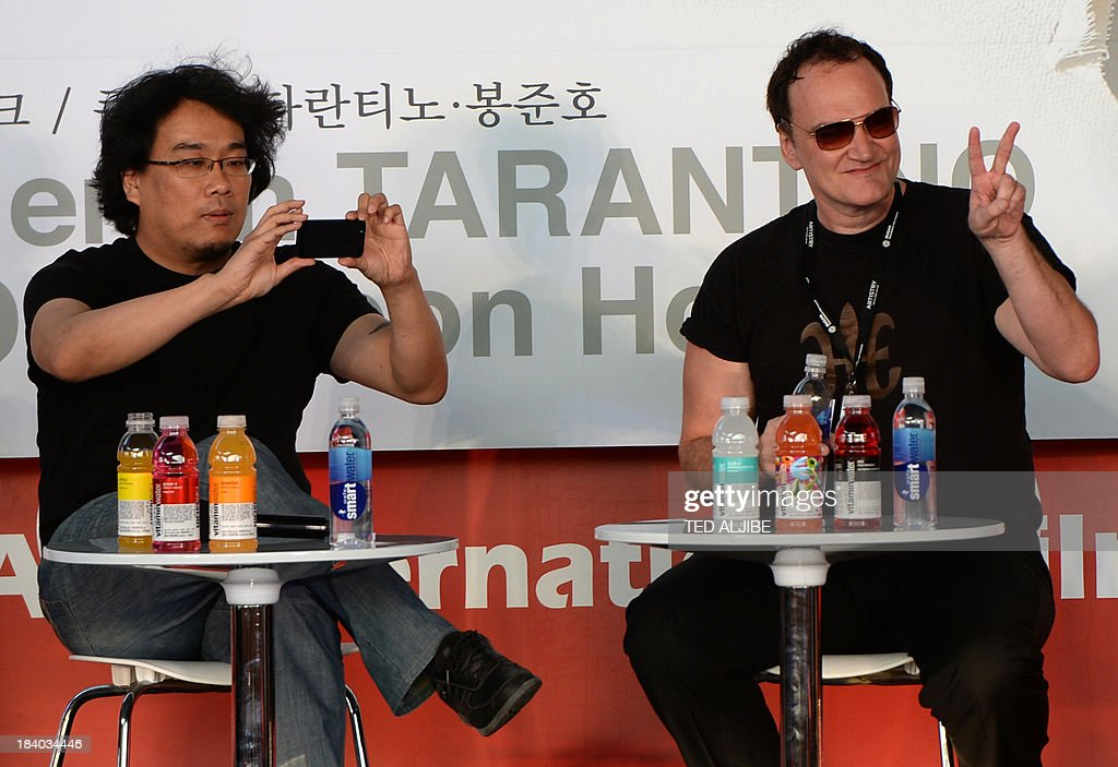 Two-times Oscar awards winner and hollywood director Quentin Tarantino (R) gestures to fans while South Korean director Bong Joon-Ho (L) uses his mobile phone to take a photo during the open talk event at the 18th Busan International Film Festival (BIFF) in Busan on October 11, 2013. The Busan film festival is being held from October 2-12.