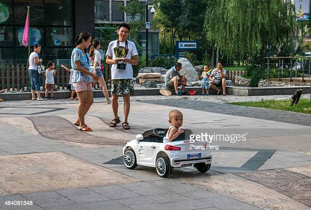 A twoyear old boy sit on an electric toy car which is remotecontrolled by his parent following behind China is considering whether to allow all...