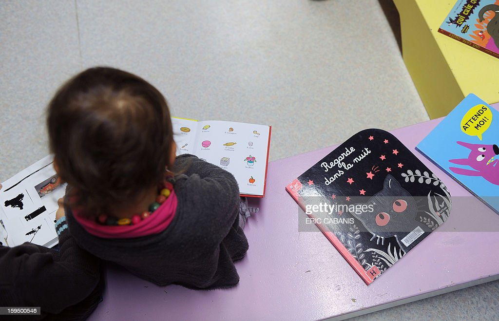 A two-year-old child looks at a book at a kindergarten in Firmi, central southern France, on January 14, 2013. French government is expected to announce in the coming days schooling for toddlers (children less than three years).
