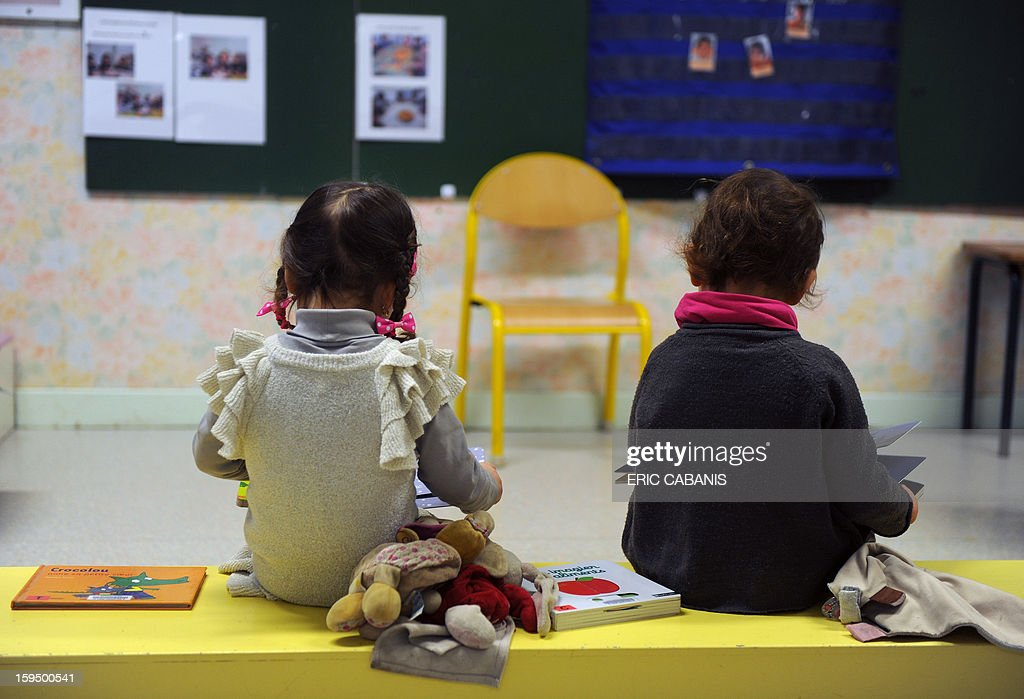 Two-year-old children look at books at a kindergarten in Firmi, central southern France, on January 14, 2013. French government is expected to announce in the coming days schooling for toddlers (children less than three years).