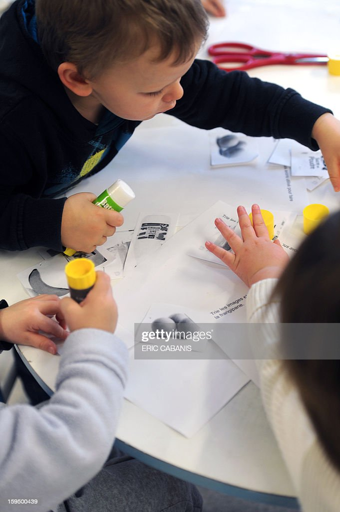 Two-year-old children make collages at a kindergarten in Firmi, central southern France, on January 14, 2013. French government is expected to announce in the coming days schooling for toddlers (children less than three years). AFP PHOTO / ERIC CABANIS CAPTION