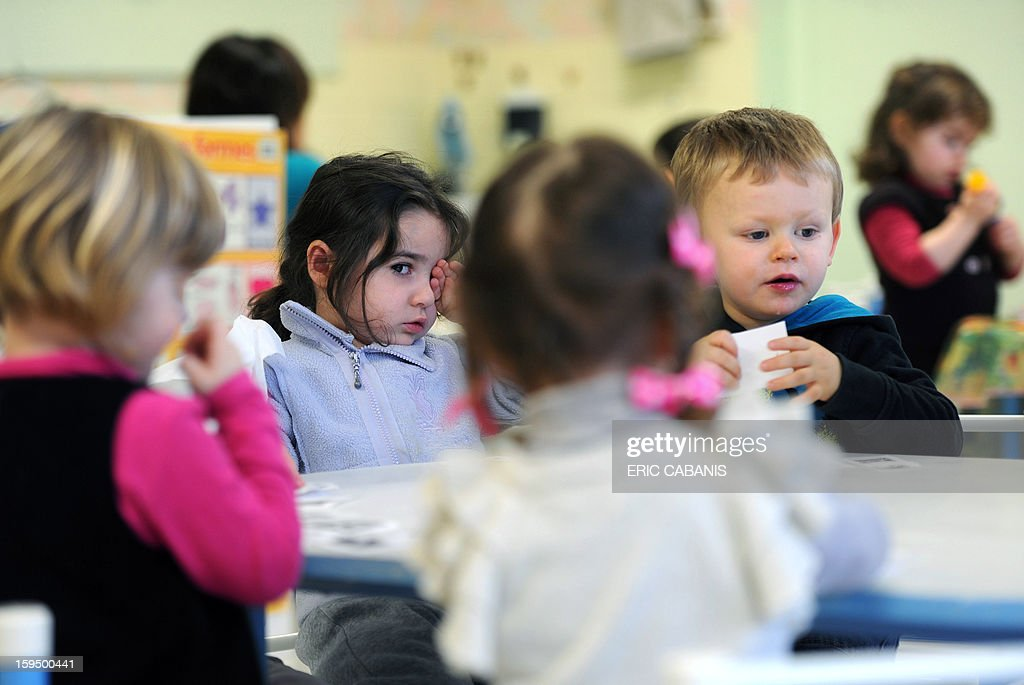 Two-year-old children sit around a table at a kindergarten in Firmi, central southern France, on January 14, 2013. French government is expected to announce in the coming days schooling for toddlers (children less than three years).