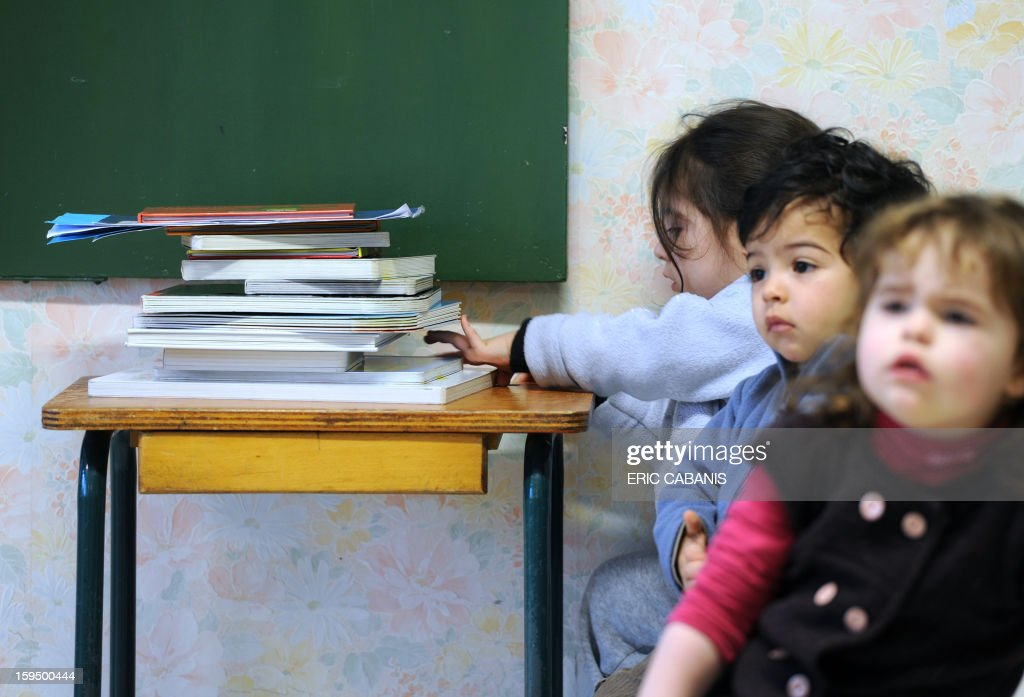 Two-year-old children sit around tables at a kindergarten in Firmi, central southern France, on January 14, 2013. French government is expected to announce in the coming days schooling for toddlers (children less than three years). CAPTION