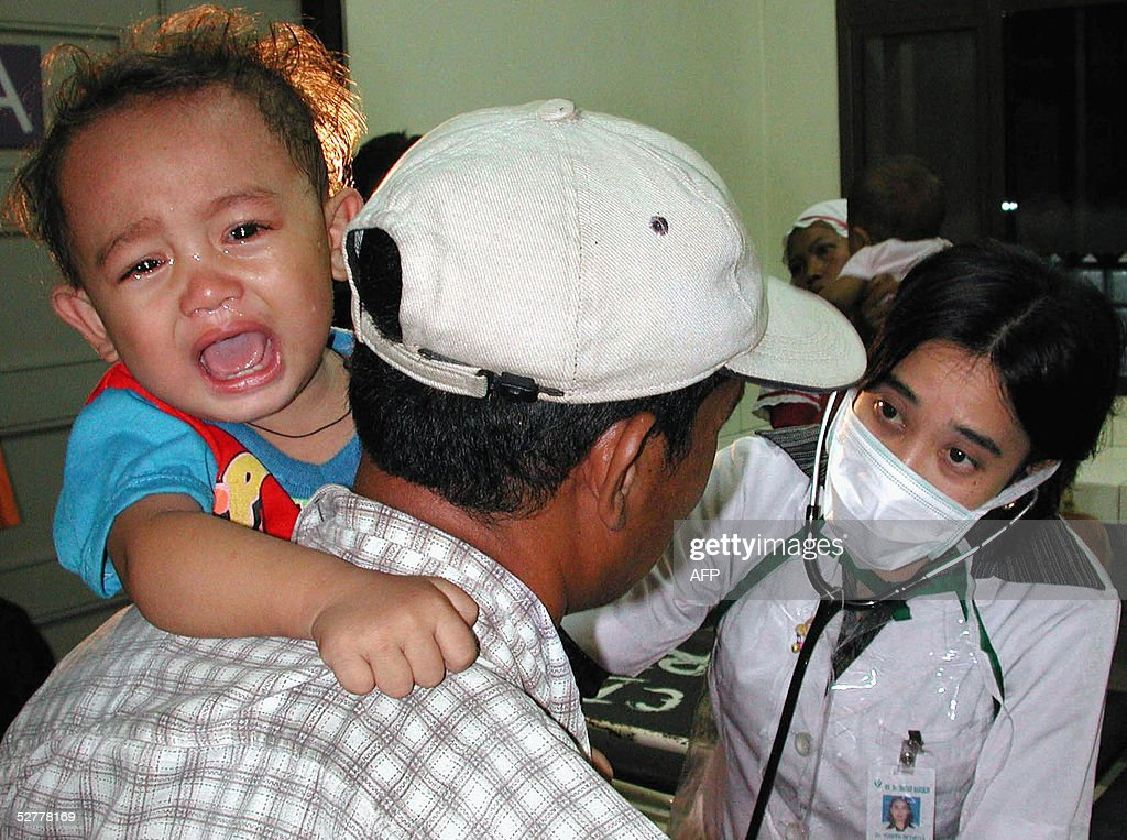 Two-year-old Ismail (L), one of six infants from Cidahu village in West Java found to be infected with polio, is held by his father (C) during an examination from a doctor in Bandung, West Java, 09 May 2005. At least six infants have been confirmed to suffer from polio in the district just south of Jakarta, the first cases of the disease to have been found since 1995.