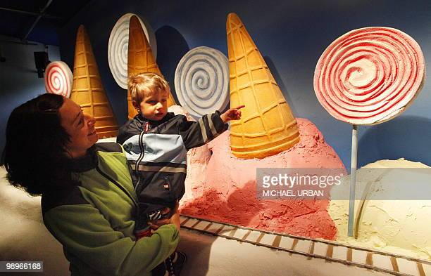 Twoyears old Theo and his mother Sarah look at giant mockups of icecream and lollipops presented in an exhibition at the Filmpark Babelsberg on May...