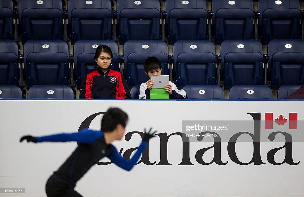 Ty(R) (11) and Alexa (14) Bravong of London, Ontario watch as Jin Seo Kim of Korea practices in preparation for the 2013 World Figure Skating Championships in London, Ontario, Canada, March 11, 2013. The competition starts on Wednesday. AFP PHOTO/Geoff Robins