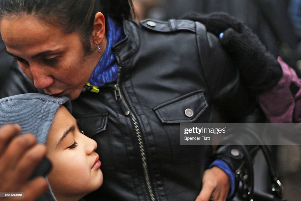 Ty Diaz is kissed by his mother Yvette at a memorial down the street from the Sandy Hook School December 16, 2012 in Newtown, Connecticut. Twenty-six people were shot dead, including twenty children, after a gunman identified as Adam Lanza opened fire at Sandy Hook Elementary School. Lanza also reportedly had committed suicide at the scene. A 28th person, believed to be Nancy Lanza, found dead in a house in town, was also believed to have been shot by Adam Lanza.