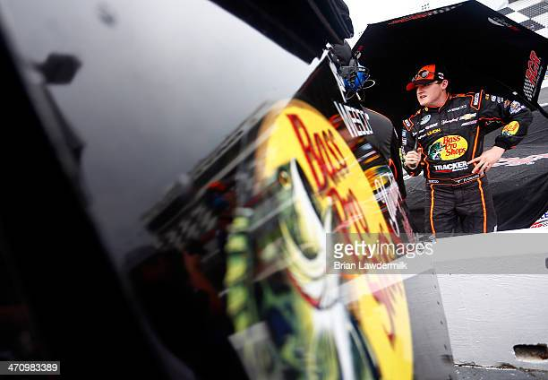 Ty Dillon driver of the Bass Pro Shops/Tracker Boats Chevrolet uses an umbrella to sheild himself from rain during qualifying for the NASCAR...