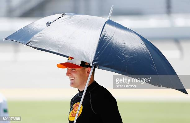 Ty Dillon driver of the Bass Pro Shops/TRCKR BTS Chevrolet stands on the grid with an umbrella during qualifying for the NASCAR XFINITY Series...