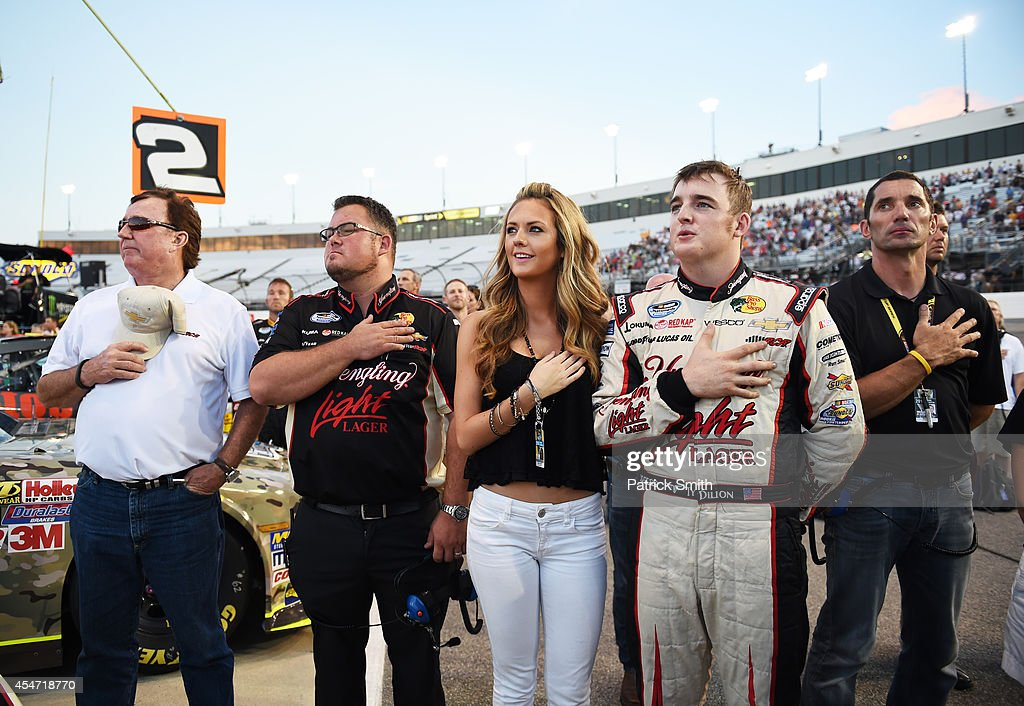 Ty Dillon driver of the Yuengling Light Lager Chevrolet right takes part in prerace ceremonies with girlfriend Haley Carey and team owner grandfather...