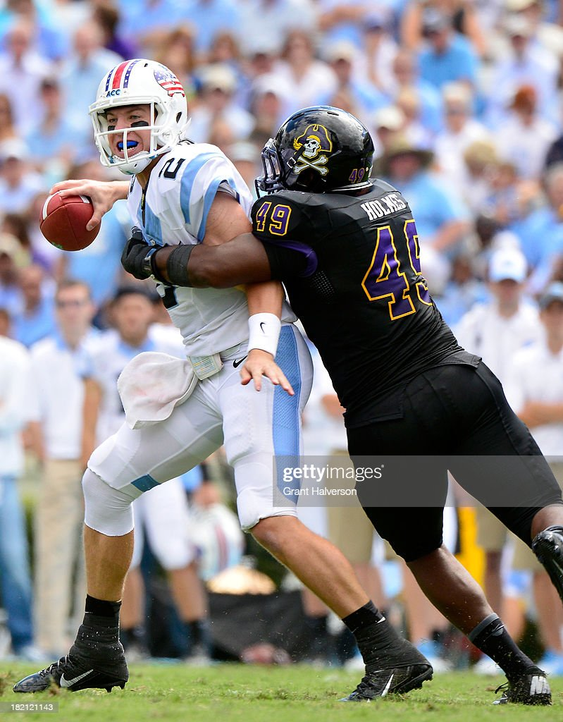 Ty Holmes #49 of the East Carolina Pirates pressures Bryn Renner #2 of the North Carolina Tar Heels during play at Kenan Stadium on September 28, 2013 in Chapel Hill, North Carolina.