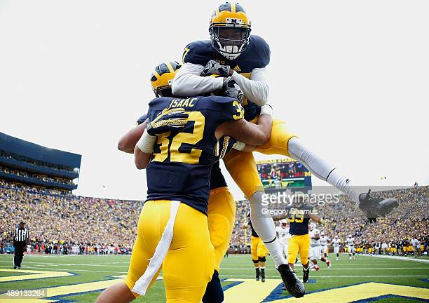 Ty Isaac of the Michigan Wolverines celebrates a second quarter touch down with Freddy Canteen while playing the UNLV Rebels on September 19 2015 at...
