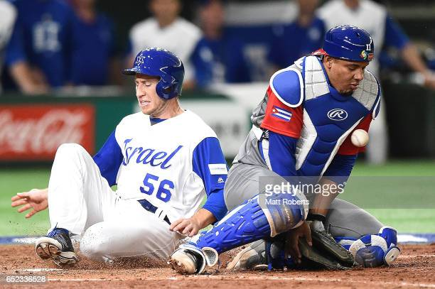 Ty Kelly of Israel scores as catcher Frank Morejon of Cuba tries to tag out after Zach Borenstein of Israel hits a RBI single grounder to right...