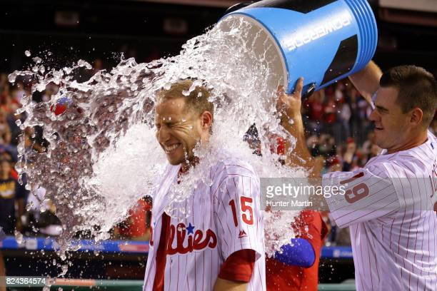 Ty Kelly of the Philadelphia Phillies is doused with water by Tommy Joseph after hitting a game winning walkoff RBI single in the 11th inning during...