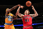 Ty Lawson of the Denver Nuggets and Cameron Bairstow of the Chicago Bulls battle for a rebound at Pepsi Center on November 25 2014 in Denver Colorado...
