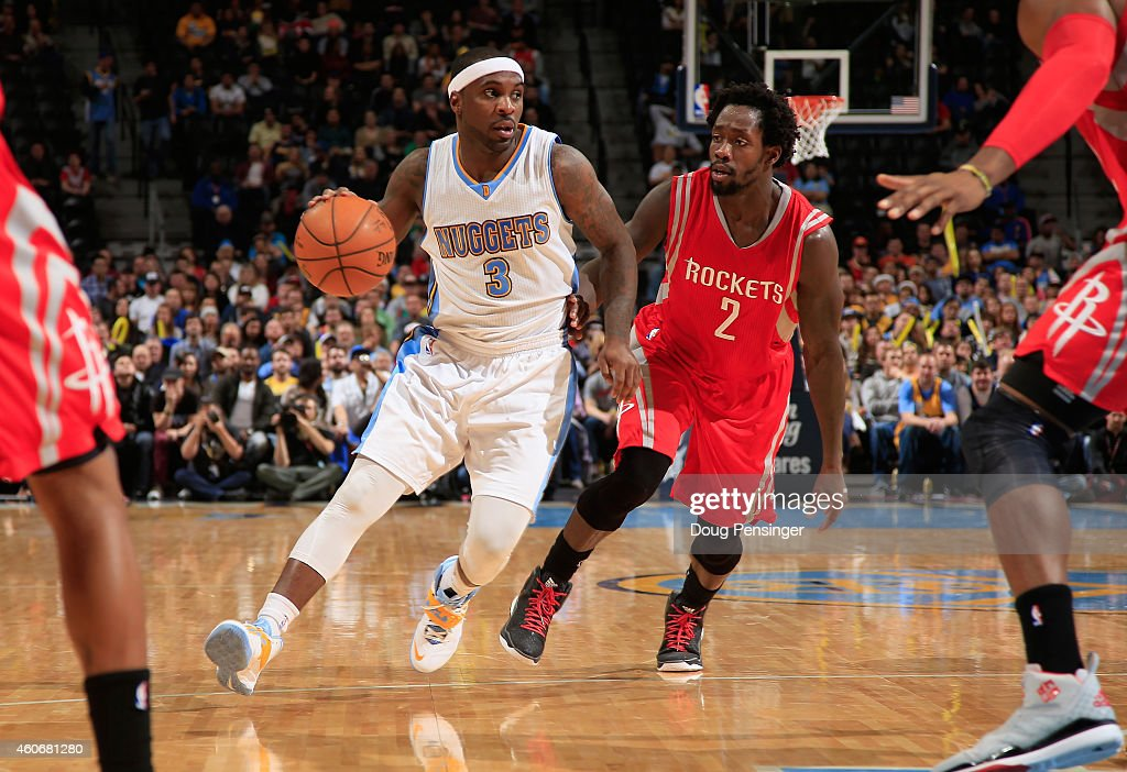 Ty Lawson of the Denver Nuggets controls the ball against Patrick Beverley of the Houston Rockets at Pepsi Center on December 17 2014 in Denver...
