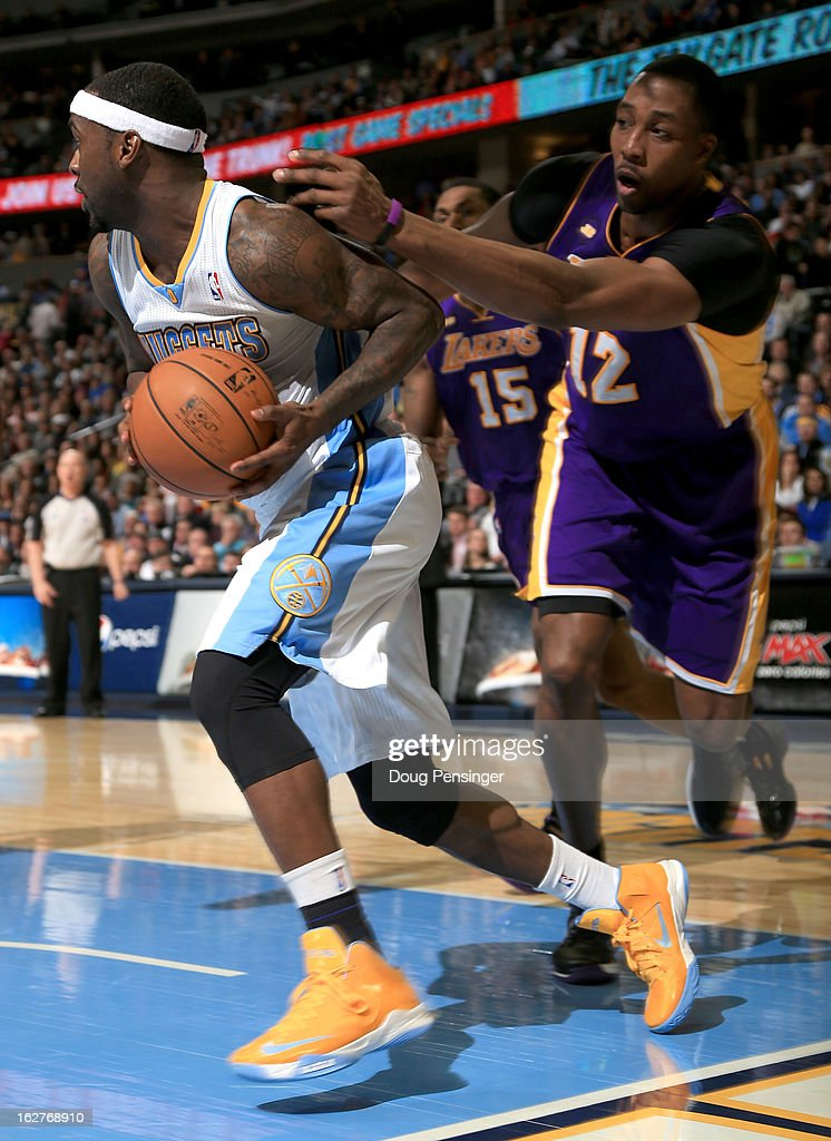 Ty Lawson #3 of the Denver Nuggets controls the ball while under pressure from Dwight Howard #12 of the Los Angeles Lakers at the Pepsi Center on February 25, 2013 in Denver, Colorado. The Nuggets defeated the Lakers 119-108.