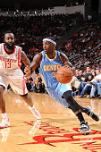 Ty Lawson of the Denver Nuggets drives the ball against James Harden of the Houston Rockets on November 16 2013 at the Toyota Center in Houston Texas...