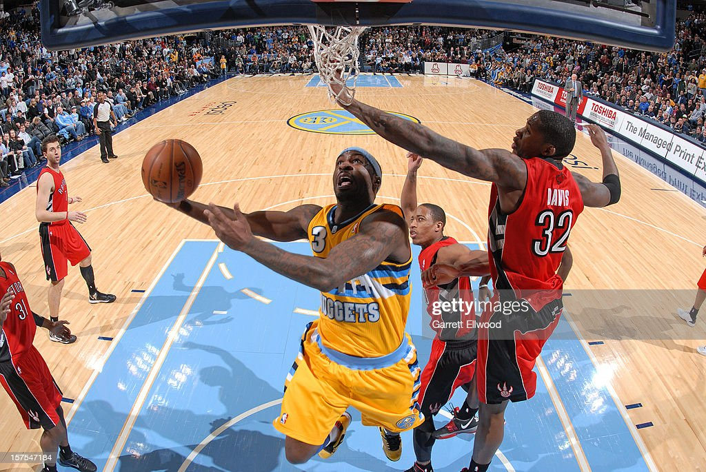 Ty Lawson #3 of the Denver Nuggets drives to the basket against Ed Davis #32 of the Toronto Raptors on December 3, 2012 at the Pepsi Center in Denver, Colorado.